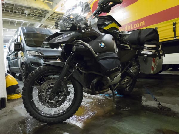 Mitten auf dem Lastwagendeck steht ein einsames Motorrad
